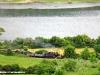 La FCS 400 delle Ferrovie della Sardegna effettua un viaggio per l'operatore inglese Railways Touring Company con un treno composto dalla carrozza Bauchiero, un bagagliaio e un carro a sponde alte, qui ripreso sulla Mandas-Arbatax all'altezza del Lago del Medio Flumendosa. (22/05/2010; foto Mario Dessì; foto Mario Dessì / tuttoTreno)
